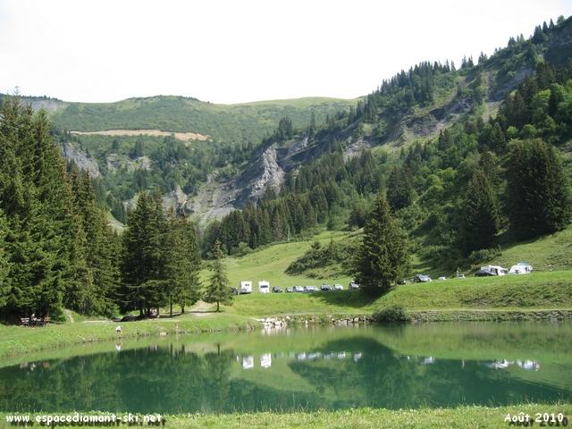 Le Lac de Plan Dessert avec les barres rocheuses du massif du Crêt du Vorès en arrière plan